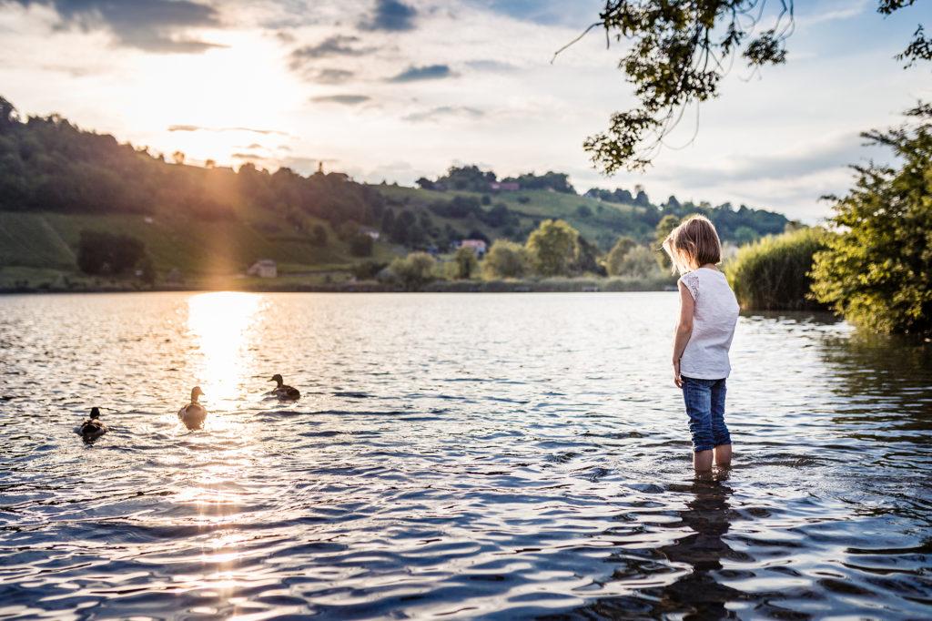 Enfant au coucher de soleil au lac de Saint André en Savoie